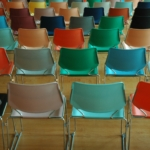 The backs of cheerful colored chairs in a waiting room for a UK visa processing centre, queues can be avoided by etting Butler and BRewer help you with your visa appliction